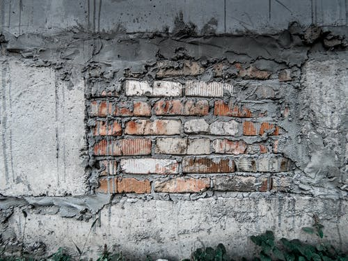 Aged grunge wall with bricks and gray concrete blocks in plaster and cement