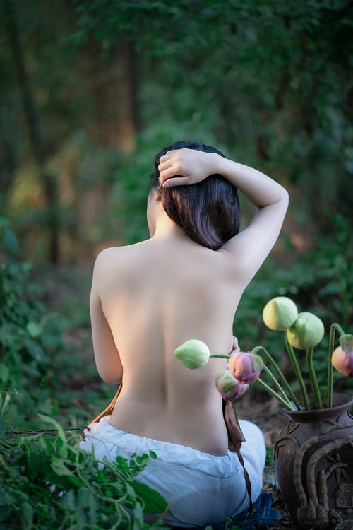 Sensual woman with flowers in garden