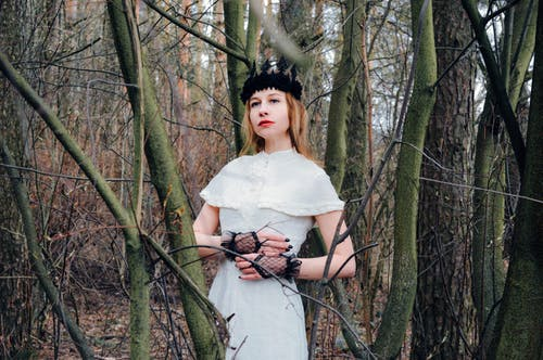 Melancholy elegant woman in mysterious woods
