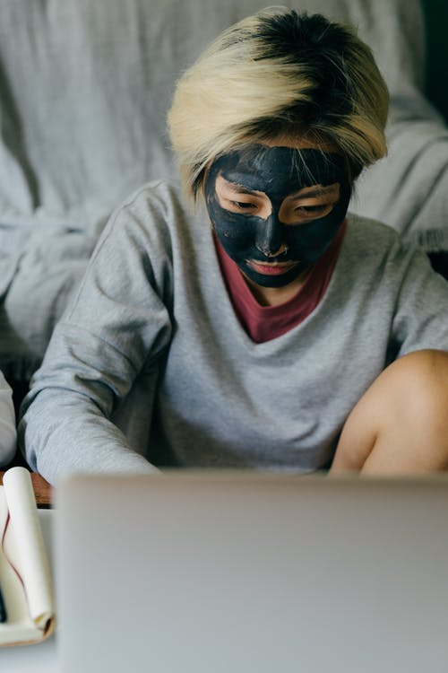 Young woman with facial mask using laptop at home