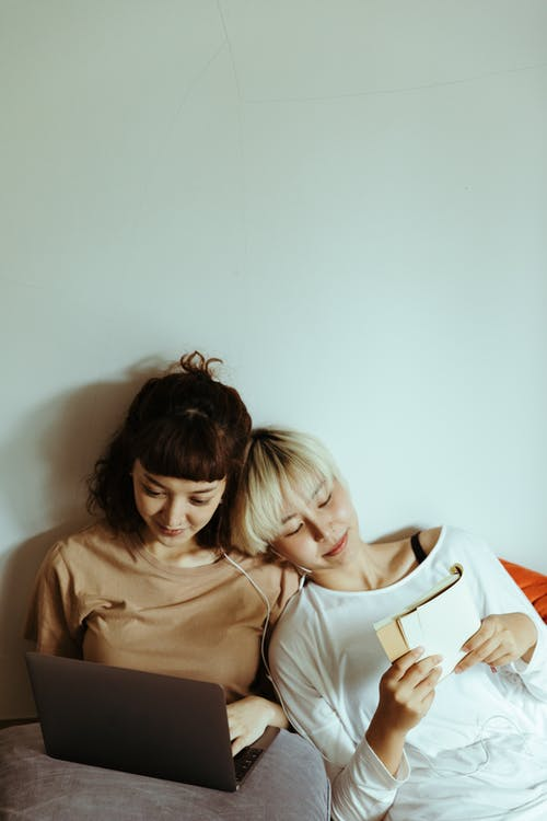 Positive young Asian sisters wearing casual clothes using modern netbook and reading book while lying on floor beside each other against gray wall