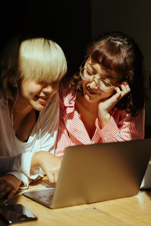 Cheerful sisters using laptop together