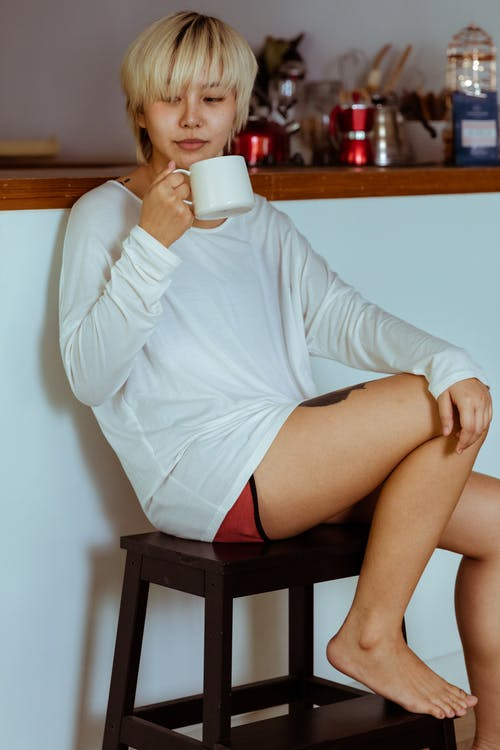 Calm woman drinking hot beverage on stool