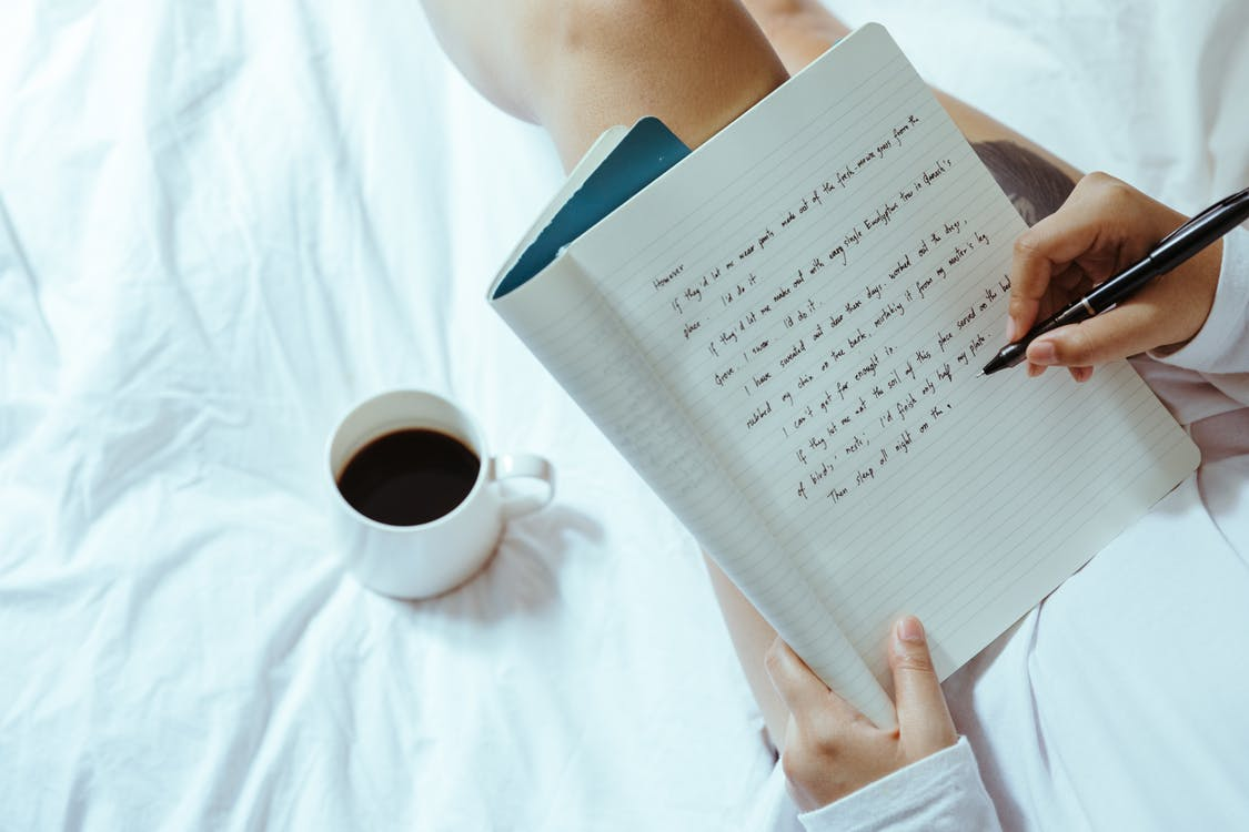 Top view of unrecognizable woman sitting on bed with legs near cup of coffee and writing on notepad with pen while resting at home