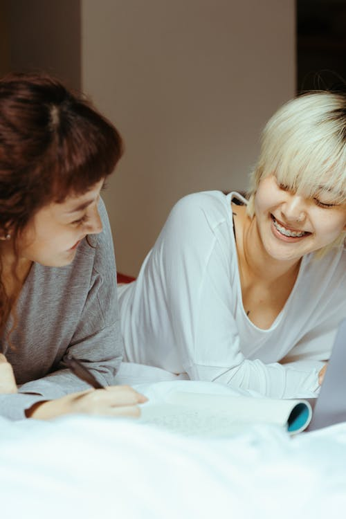 Happy young ethnic women in sleepwear smiling and relaxing in comfortable bed while reading diary and taking notes in modern bedroom