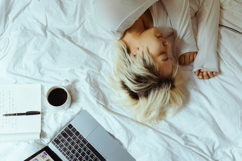 From above ethnic woman lying on bed with laptop coffee and notebook resting while brake in comfortable bedroom at home in weekend