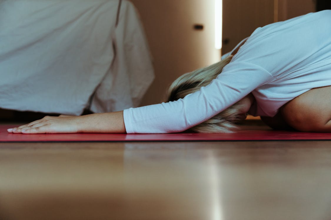 Young female practicing yoga at home wearing casual clothes and stretching body while doing extended child asana during weekend at morning time