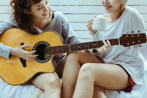 Girlfriends with guitar resting together on cozy terrace