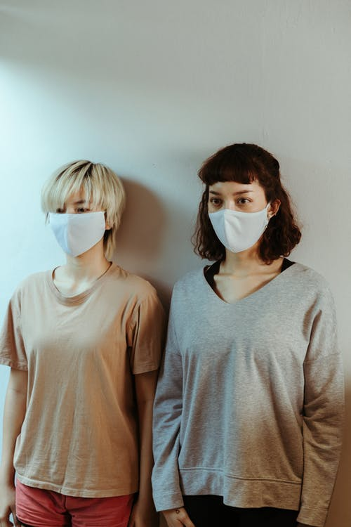 Asian women in home wear in medical masks attentively looking away while standing against white wall