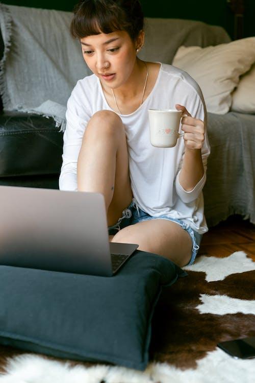 Asian female freelancer working on laptop in living room