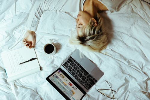 Student sleeping on bed near laptop and cup of coffee