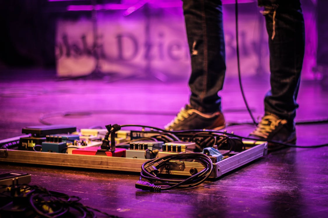 Faceless musician with pedalboard in club