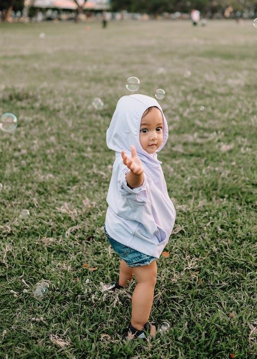 Little child reaching arm in green field under soap bubbles