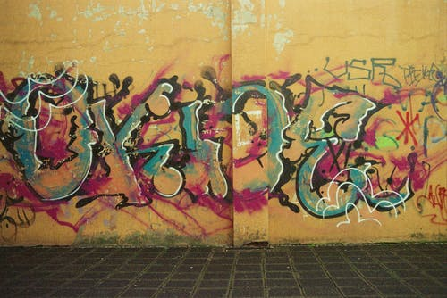 Painted artwork representing multicolored graffiti with letters and wavy messy lines on aged concrete wall near tiled pavement on city street in daylight