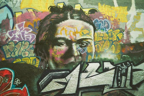 Creative bright graffiti of human face on wall in town