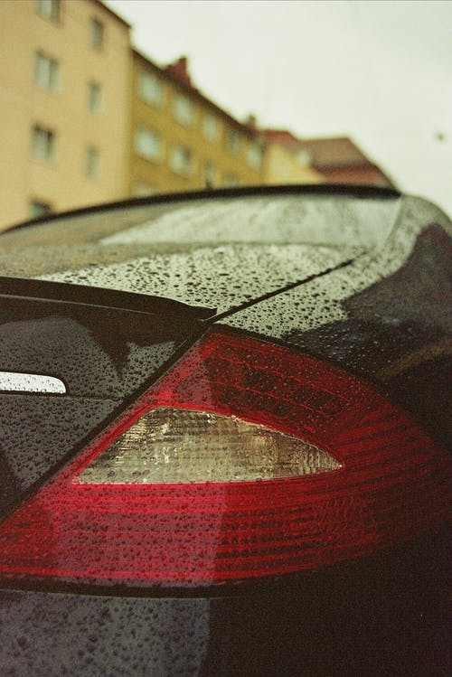 Rear bumper of modern style black car with red taillight and water drops on shiny surface on city street near multistory residential house facade on rainy day