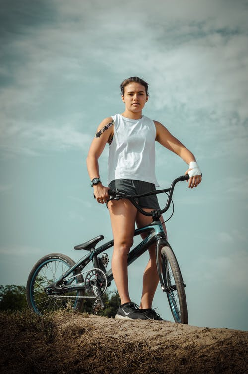 Woman in White Tank Top Riding on Black Bicycle