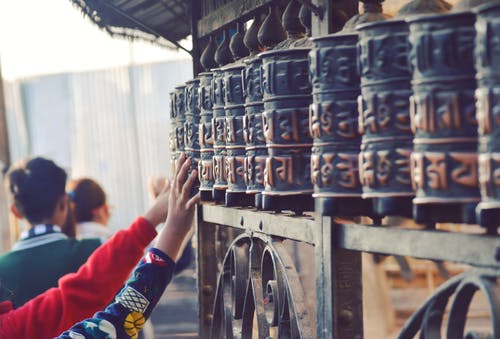 Back view of anonymous tourists touching old metal Prayer wheels with hieroglyphs above ornamental fence near old Buddhist temple in Swayambhunath