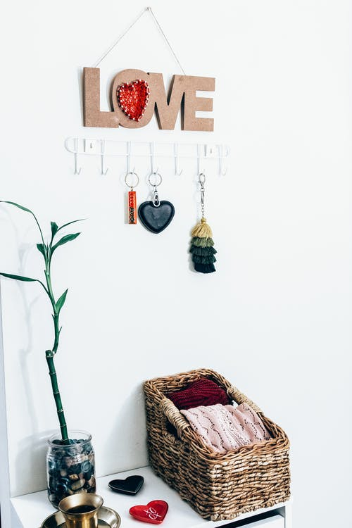Decorative Love key holder above wicker box with fabric on table with vase and decorations at home