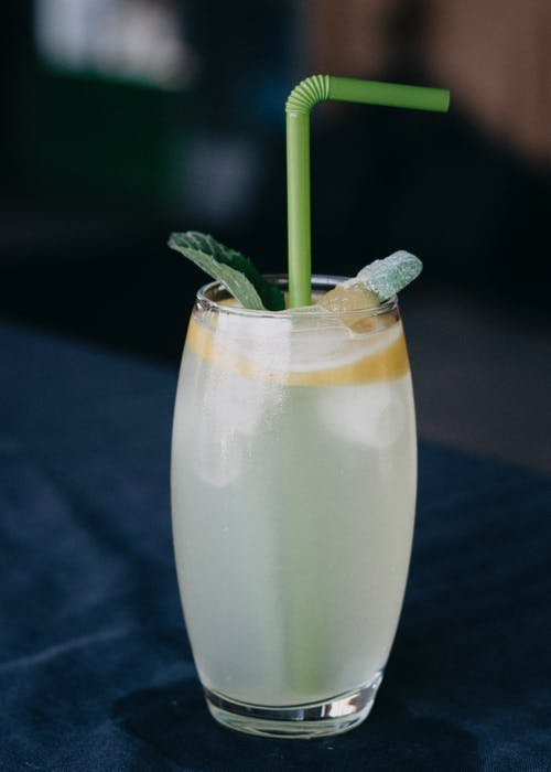 Clear Drinking Glass With Green Straw