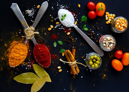 Top view of dry turmeric and paprika near bay leaves with cinnamon sticks and sea salt in spoons near jars with popcorn grains and olives with ripe colorful cherry tomatoes
