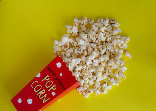 Pack with spilled popcorn on yellow background