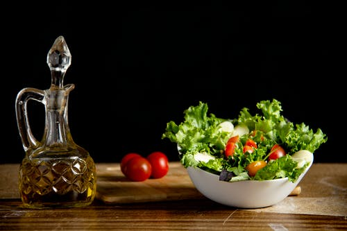 Vitamin vegetable salad on table with bottle of oil