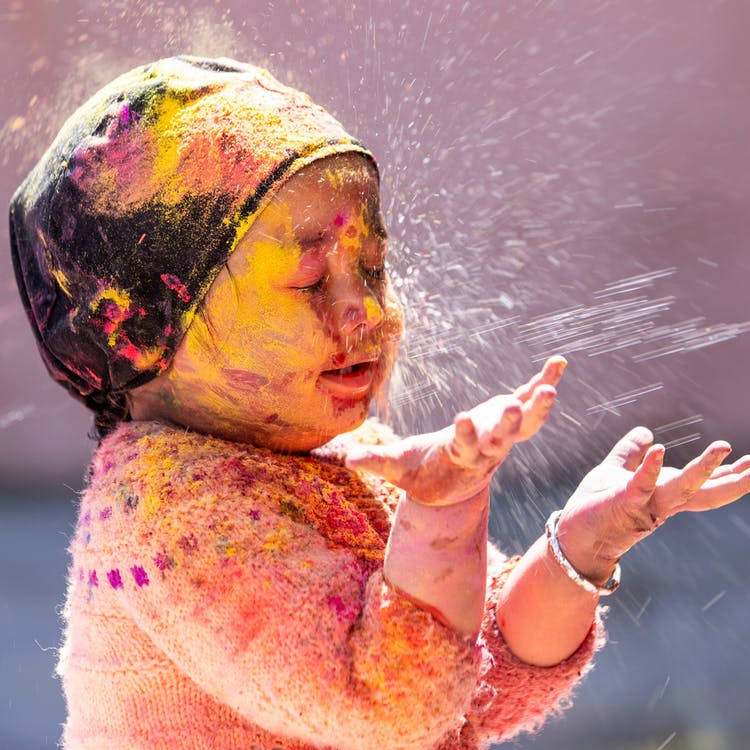 Side view of charming ethnic kid in headscarf and knitted sweater standing with closed eyes all covered multicolored powder during religious Hindu holiday