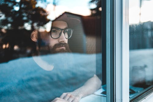 Through glass view of crop young trendy contemplative hipster male in eyeglasses and cap looking away through window while sitting near windowsill in daylight