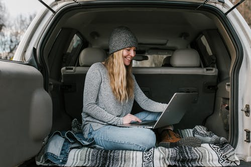 Woman in Gray Sweater and Blue Denim Jeans Sitting on Car Seat