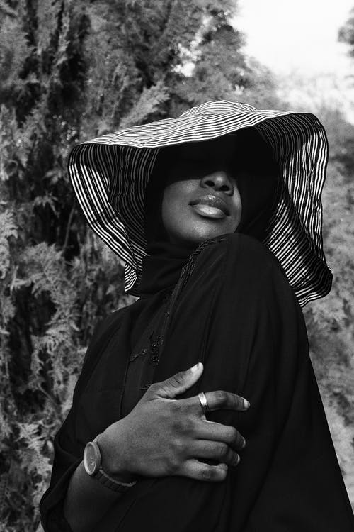 Anonymous elegant black lady in hat embracing herself behind trees