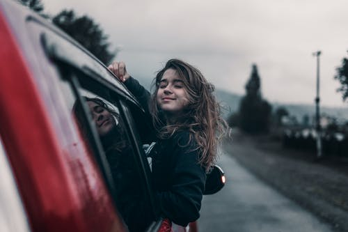 Side view of young dreamy ethnic female with closed eyes leaning out automobile window driving on asphalt road near trees and mountains under sky in countryside