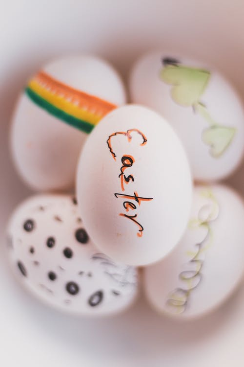 From above of white painted eggs with word and decorative blots with bright heart symbol on surface in flat during Easter