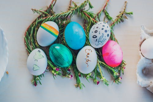 Top view composition of various colorful eggs placed on green twigs on white table