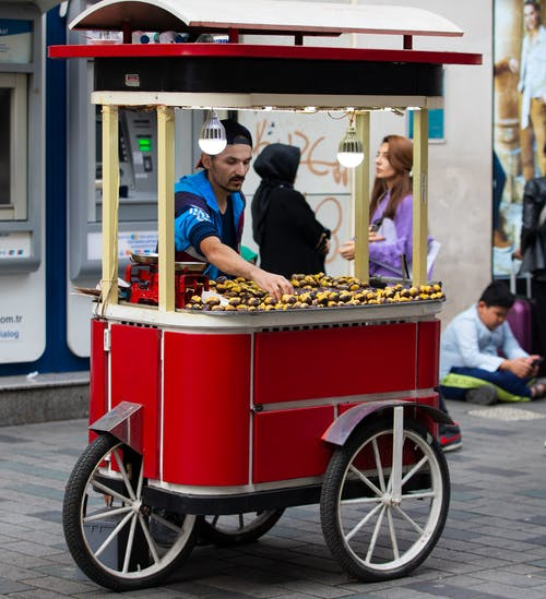 Ethnic man selling food on city street