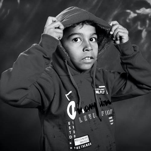 Thoughtful ethnic boy in hoodie looking away