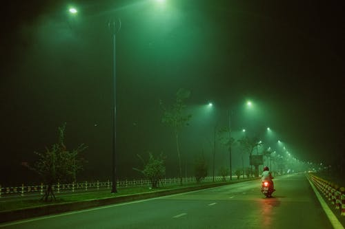 Unrecognizable person riding motorcycle at night