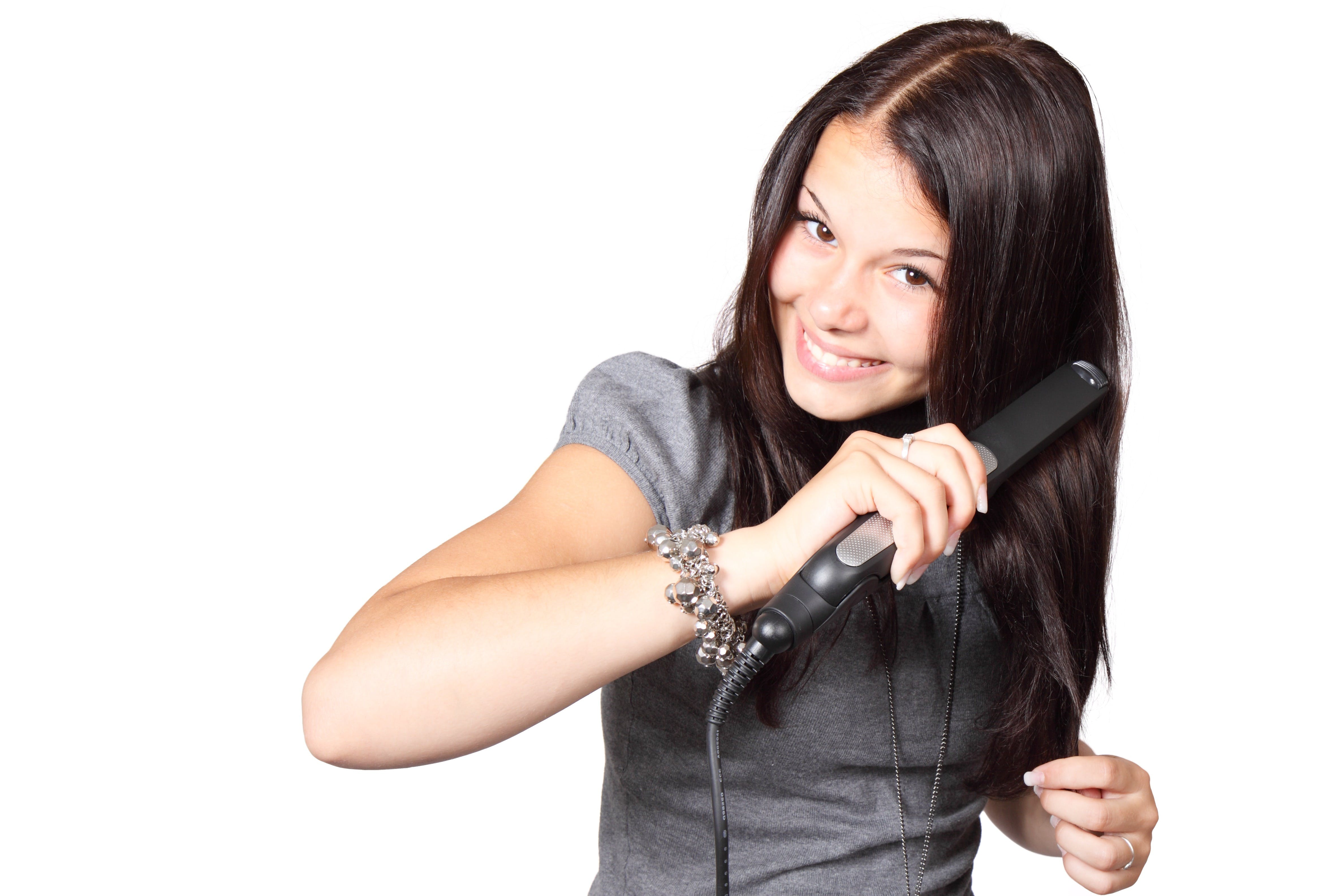 Woman in Gray Shirt Straightening Her Hair
