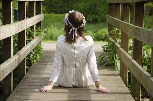 Woman Sitting on Brown Wooden Bridge