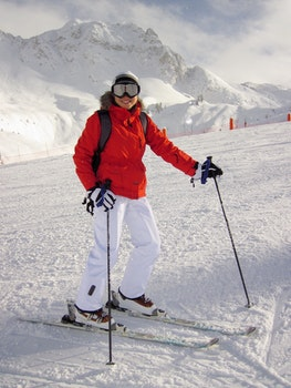 Woman in Red Jacket and White Pants on White Snow