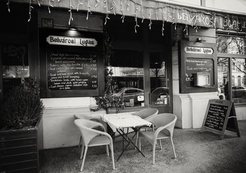 Black and white of street terrace of modern cafeteria with comfortable chairs and menu boards in city