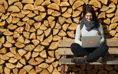 Full body of positive young female freelancer in casual clothes sitting on wooden bench with crossed legs and working remotely on laptop against creative lumber wall on sunny day