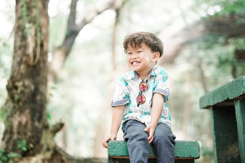 Boy in Floral Button Up T-shirt Sitting on Green Concrete Bench