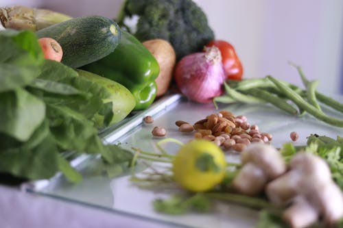 From above of various fresh organic colorful vegetables and nuts placed on glass tabletop in light kitchen