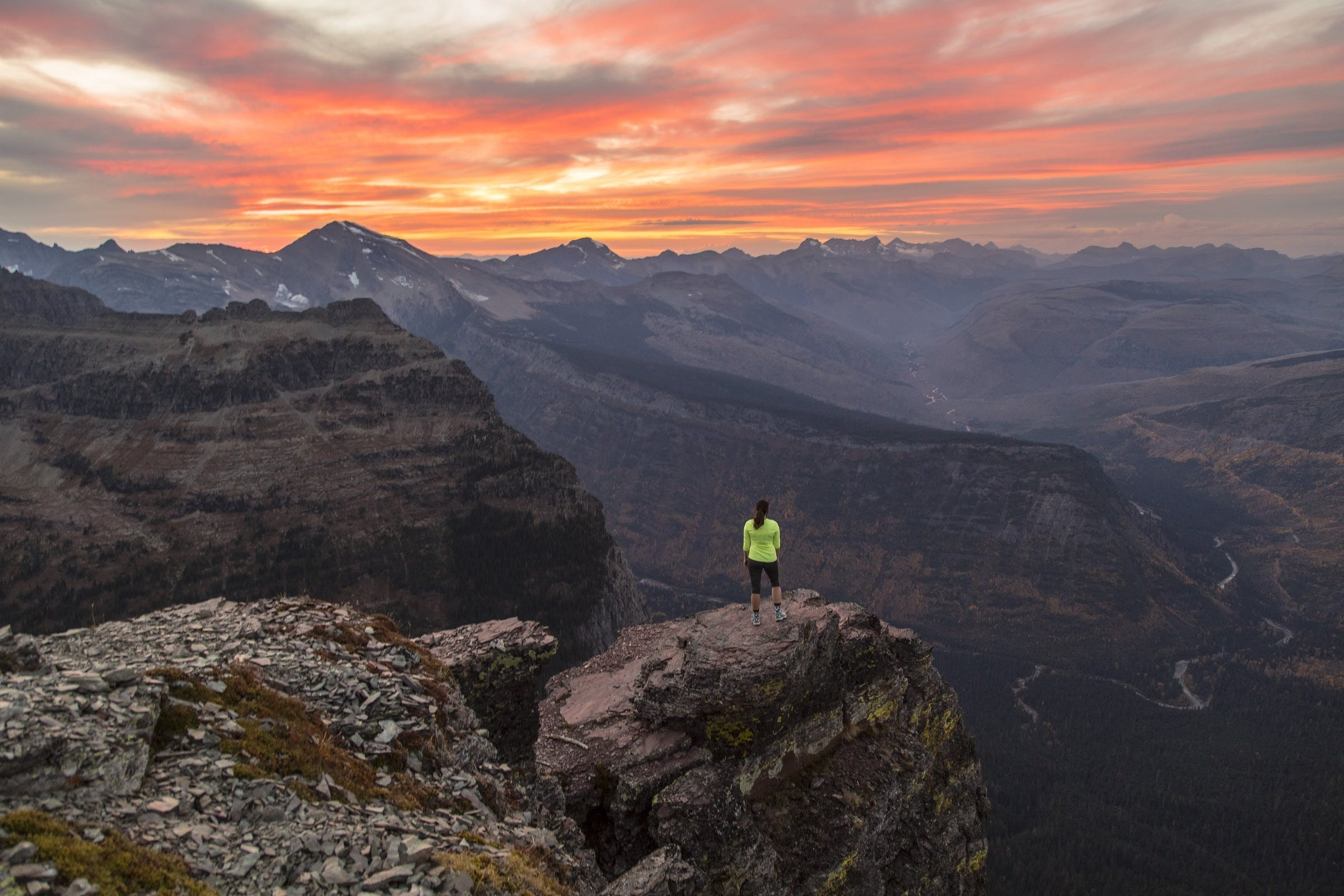 Woman Standing on Edge of Mountain