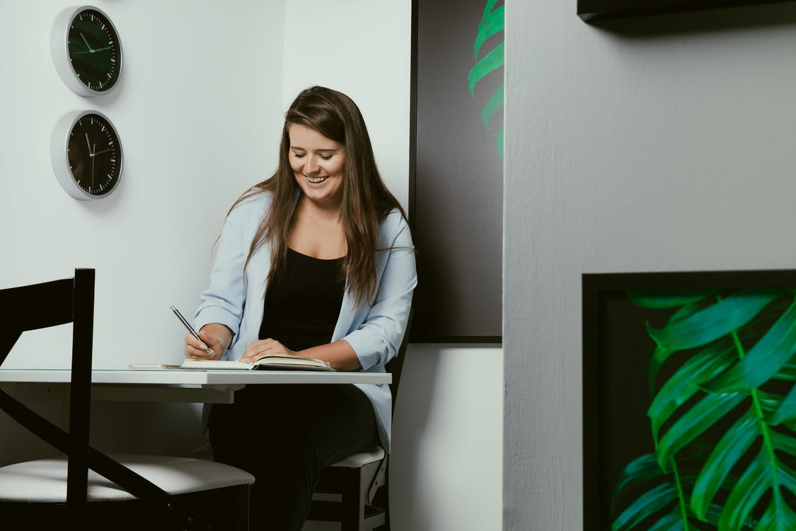 Happy young female freelancer writing in notebook in modern workspace