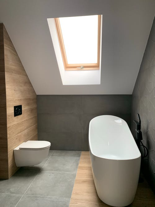 Modern interior of stylish minimal attic bathroom with white bathtub and toilet and roof window