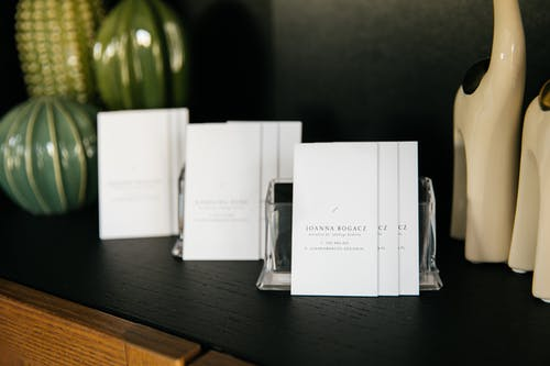 Set of simple visit cards on shelf composed with various stylish vases and decorative figurines in modern office