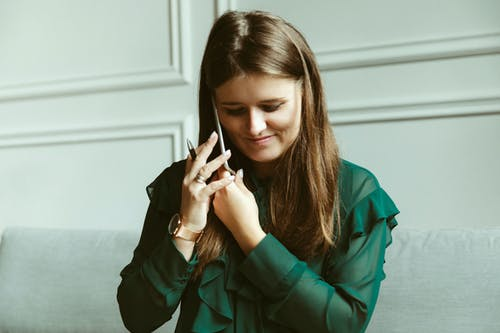 Stylish young female employee talking on smartphone in workspace