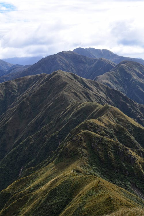 Peaks of steep mountains under cloudy sky